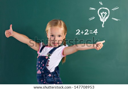 little beautiful blond girl with pigtail  showing thumbs up, from back blackboard - stock photo