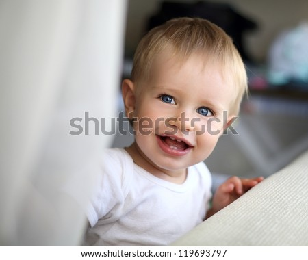 little beautiful boy looks and laughs - stock photo