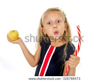 little beautiful female child with blond hair choosing dessert holding unhealthy but tasty red candy licorice and apple fruit in healthy versus unhealthy die nutrition isolated on white background - stock photo