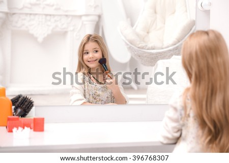 Little beautiful girl applying makeup in front of mirror. Nice cozy white bedroom. Girl using brush for makeup - stock photo
