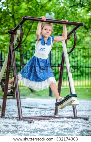 Little beautiful girl climbs on elliptical trainer at playground in summer city park. - stock photo