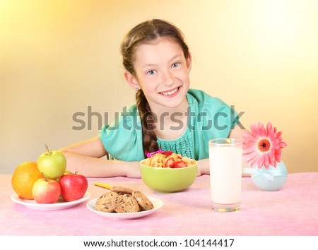 little beautiful girl have a breakfast on beige background - stock photo