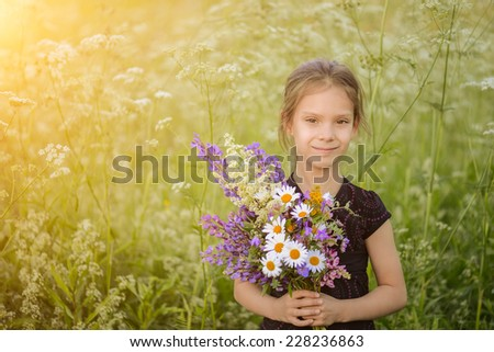 Little beautiful girl holding wildflowers on a background summer nature. - stock photo