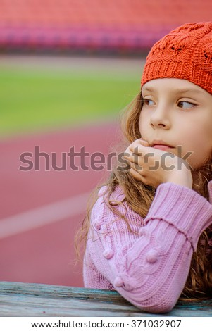 Little beautiful girl in a red cap and pink sweater has reflected on the background of a large stadium. - stock photo