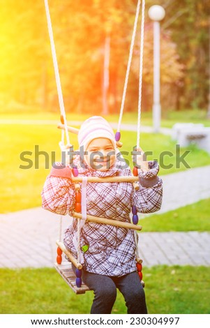 Little beautiful girl in autumn day riding on swing. - stock photo