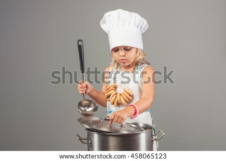 Little beautiful girl in clothes chef holding a ladle and lid from the pan on a gray background - stock photo