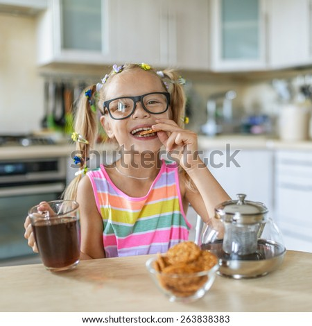 Little beautiful girl in glasses eating cookies and drinking tea on background of light dishes. - stock photo