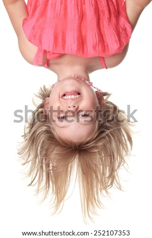 Little beautiful girl in pink clothes upside down isolated on white - stock photo