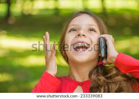Little beautiful girl in red dress laughs and talks by mobile phone, against summer city park. - stock photo