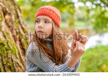 Little beautiful girl in red hat sits on background of autumn nature. - stock photo