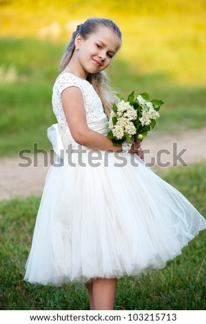 Little beautiful girl in the fashion dress in  the park - stock photo
