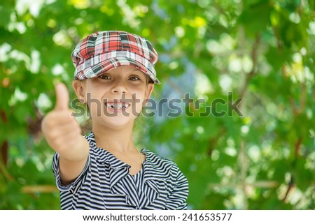 Little beautiful girl lifts thumb upwards and laughs, against background of spring green park. - stock photo