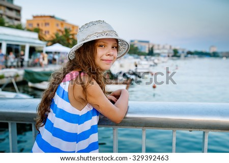 Little beautiful girl near the pier with yachts in Zadar, Central Dalmatia, Croatia. - stock photo