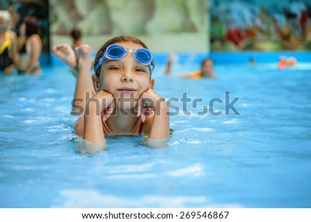 Little beautiful girl playing in the swimming pool at the resort. - stock photo