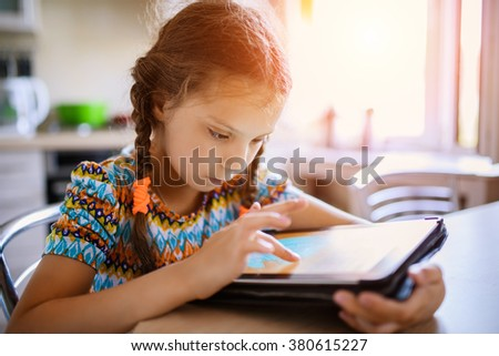 Little beautiful girl running on the tablet, sitting at the kitchen table. - stock photo