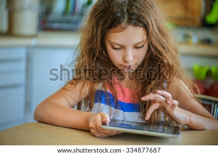 Little beautiful girl sitting at the table and working on a tablet computer. - stock photo