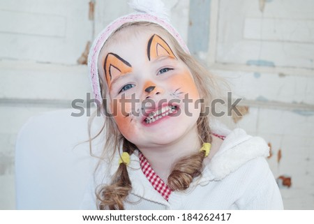 Little beautiful girl with face painting of fox unnatural smiles - stock photo