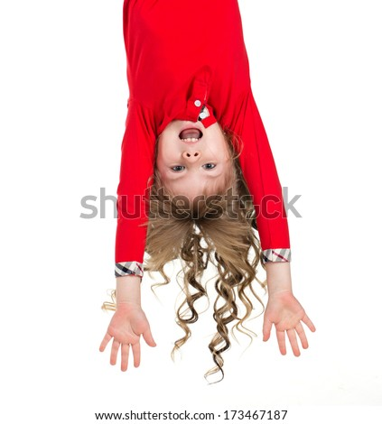 Little beautiful girl with long blond curls hanging upside down isolated on white - stock photo