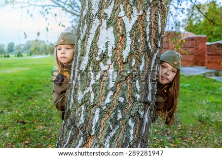 Little beautiful girls in Soviet military uniforms. - stock photo