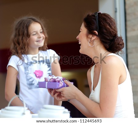 Little beautiful pretty girl giving a gift to her happy mother - indoors - stock photo