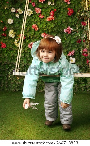 little beautiful red head girl in spring blooming garden with retro swing - stock photo