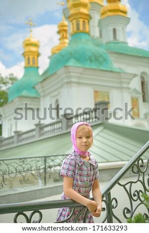 Little beautiful sad girl near Orthodox church. - stock photo
