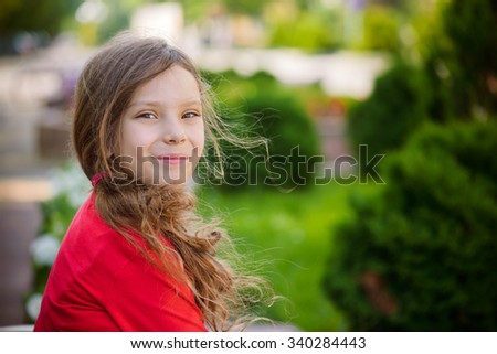 Little beautiful smiling girl in red clothes in green summer park. - stock photo