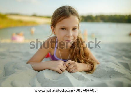 Little beautiful smiling girl lying on the warm sand on the summer beach. - stock photo