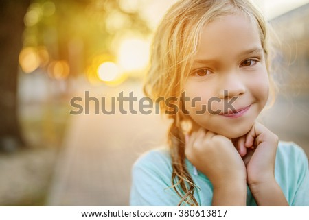 Little beautiful smiling girl on a background of a sunset on a city street. - stock photo