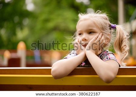 Little beautiful thoughtful girl sitting on the bench in summer green city park. - stock photo