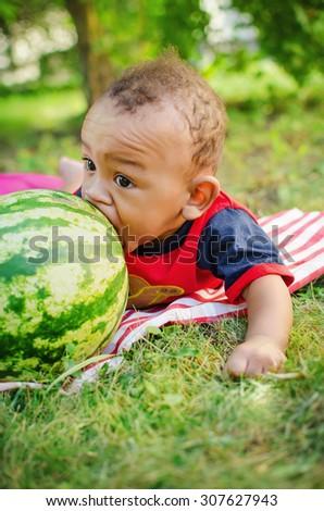 little black boy bites the big green watermelon - stock photo