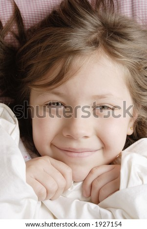 little blond and smiling girl waking up on a sunny morning - stock photo