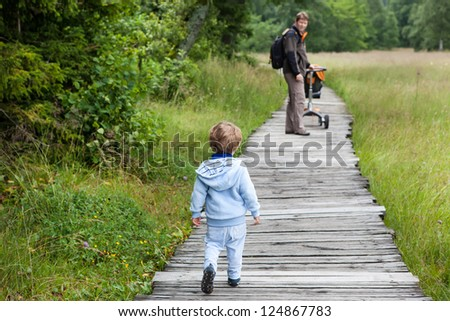 Little blond boy and his father walking through nature park summer - stock photo