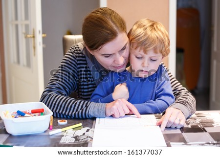 Little blond boy and his mother making together preschool homework - stock photo