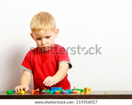 Little blond boy child kid preschooler playing with colorful building blocks toys interior. At home. Childhood and development. - stock photo