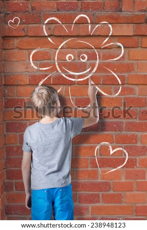 Little blond boy drawing by chalk on brick wall - stock photo