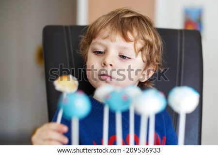 Little blond boy eating colorful cake pops, indoors. - stock photo