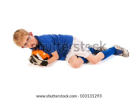 Little blond boy is playing soccer keeper in the studio - stock photo