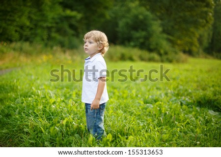 Little blond boy near forest lake on summer evening - stock photo