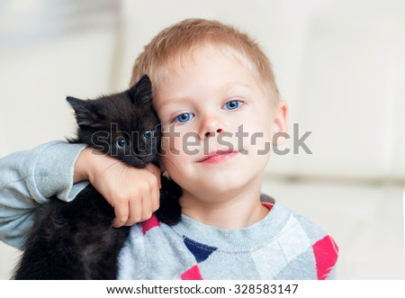 little blond boy playing with a black kitten on a white leather couch - stock photo