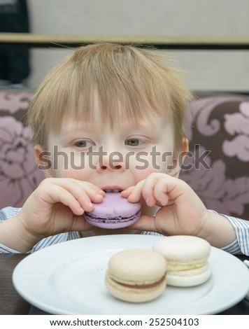 little blond boy sitting at a table eating cake - stock photo