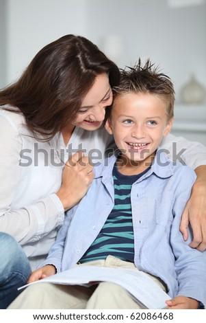 Little blond boy sitting on sofa with his mother - stock photo