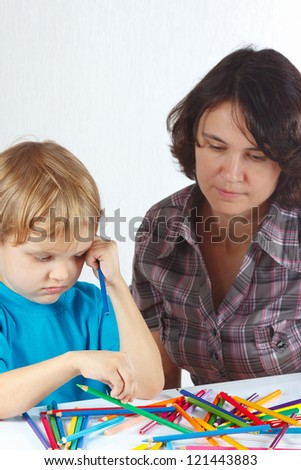 Little blond boy with his mother draws with color pencils on a white background - stock photo