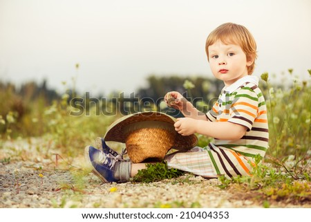 little blond boy with summer hat at rural sunset - stock photo