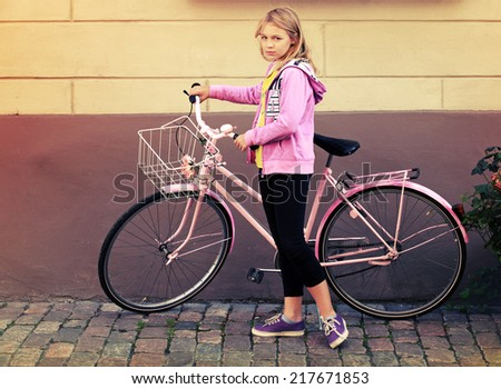 Little blond Caucasian girl in pink with bicycle, vintage toned photo - stock photo