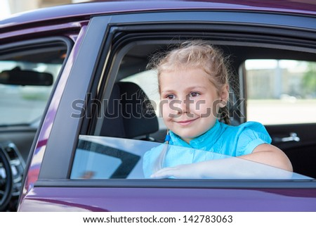 Little blond Caucasian girl looking from car window. Sitting inside of vehicle - stock photo