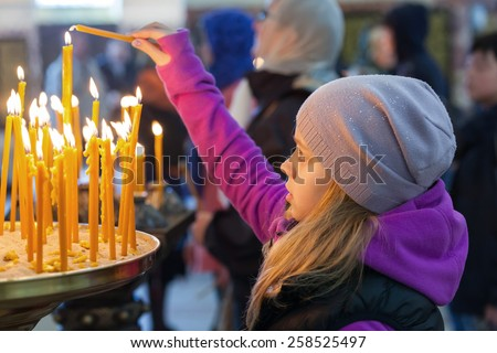 Little blond Caucasian girl with candles in Orthodox Church - stock photo