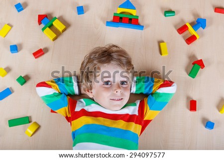 Little blond child having fun with lots of colorful wooden blocks indoor. Active kid boy wearing colorful shirt and having fun with building and creating. - stock photo