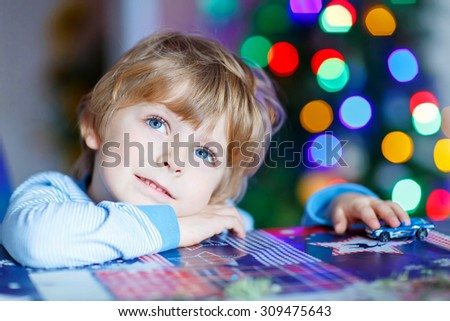 Little blond child playing with cars and toys at home, indoor. Cute happy funny boy having fun with gifts. Colorful christmas lights on background. Family, holiday, kids lifestyle concept. - stock photo
