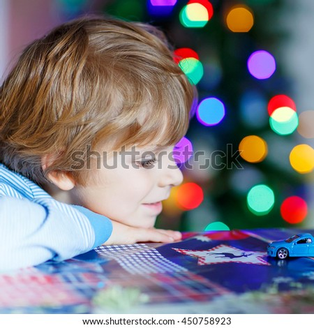 Little blond child playing with cars and toys at home, indoor. funny boy having fun with gifts. Colorful christmas lights on background. Family, holiday, kids lifestyle conceplt. - stock photo